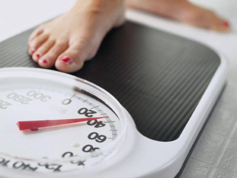 Kvinna med rött nagellack på tånaglarna ställer sig på viktvåg, svårare att hålla vikten med mycket typ 2 muskelfibrer. Muskelfibrer hålla vikten