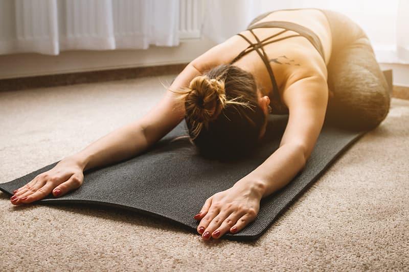 kvinna i sporttopp och yogabyxor ligger framåtlutad med händerna framför sig på en svart yogamatta på heltäckningsmatta hemma. yoga som fysisk aktivitet