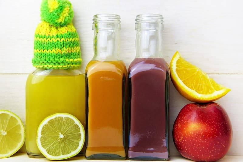 Juicer i glasflaskor med grönsaker och frukter som stärker immunförsvaret, det sitter en virkad liten hatt på ena glasflaskan