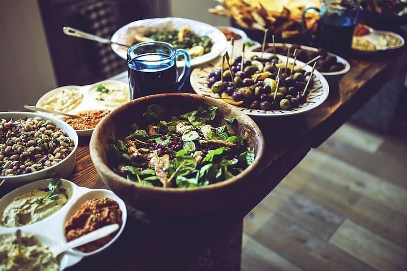 Buffe med hälsosam mat i olika skålar och på tallrikar på ett träbord, oliver, grönsaker, bönor