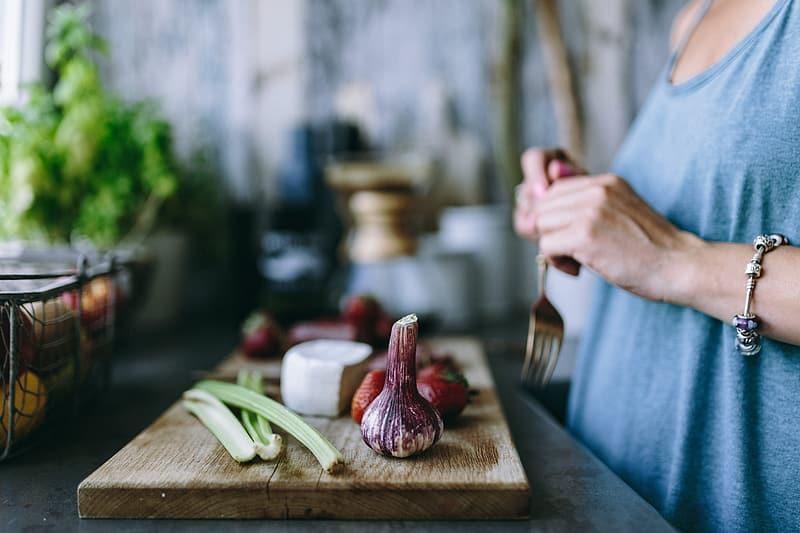 Kvinna i köket med grönsaker på skärbräda, Karolines way of life hälsoblogg