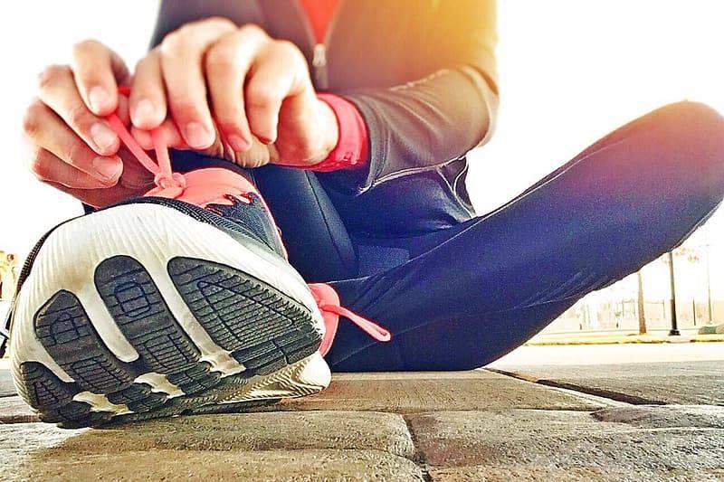 Kvinna sitter på kullerstenar och knyter träningsskor med rosa snören för att ge sig ut på träning