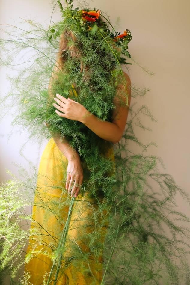 Kvinna i gul klänning står mot vägg  inlindad i gröna växter och blomkrans, örter vid klimakteriet