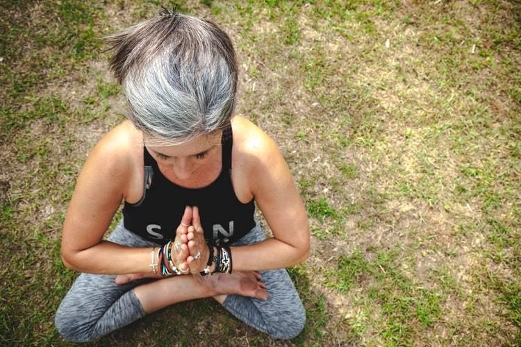 Kvinna med grått hår, svart linne och gråa träningsbyxor sitter korsad med benen och händerna mot varandra och mediterar på gräsmatta