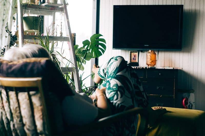 Kvinna sitter i fotölj framför tv, stillasittande, Karolines way of life hälsoblogg