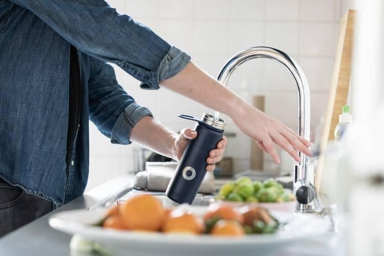 Man häller upp vatten i vattenflaska från kran, Karolines way of life hälsoblogg