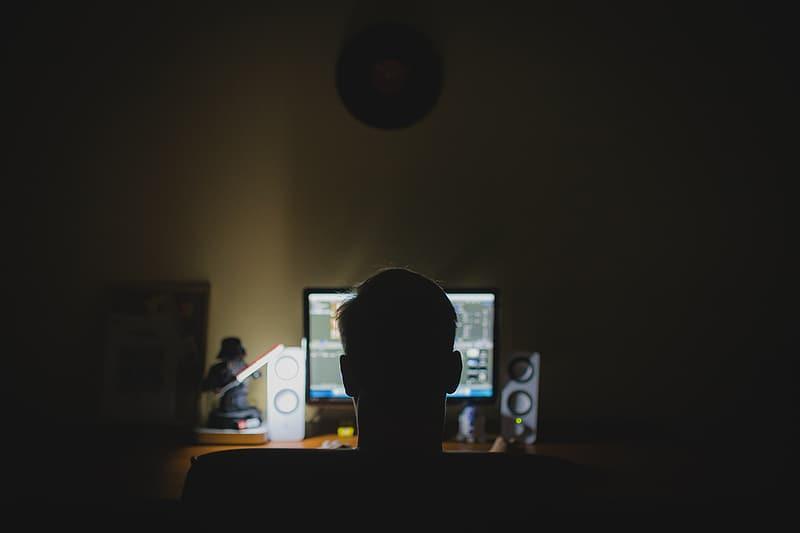 Man sitter på natten i ett mörkt rum och skapar musik på datorn, nattmänniska