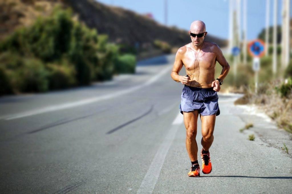 Man springer med bar överkropp i värme och solen på asfalt, långdistanslöpning, dricker tillräckligt med vätska