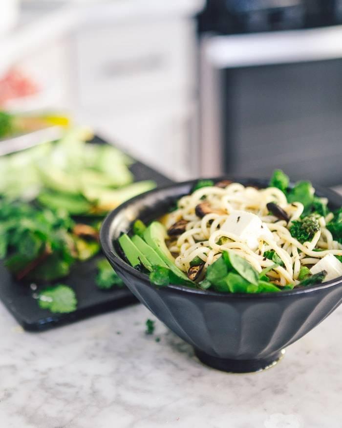 Svarta skålar med asiatisk mat med tofu soja, grönsaker och nudlar, skärbärda i bakgrunden, fytoöstrogen mat