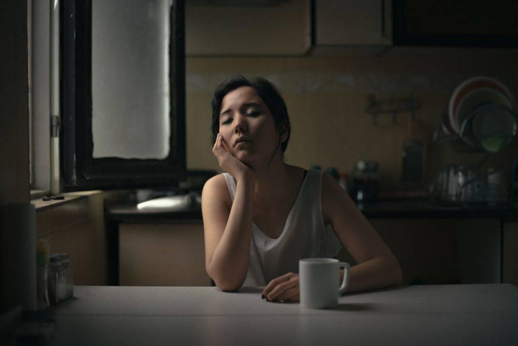 Tjej sitter trött med ögonen stängda vid borg med kopp kaffe tidigt på morgonen eller sent på kvällen, dygnsrytm, morgonmänniska eller nattmänniska