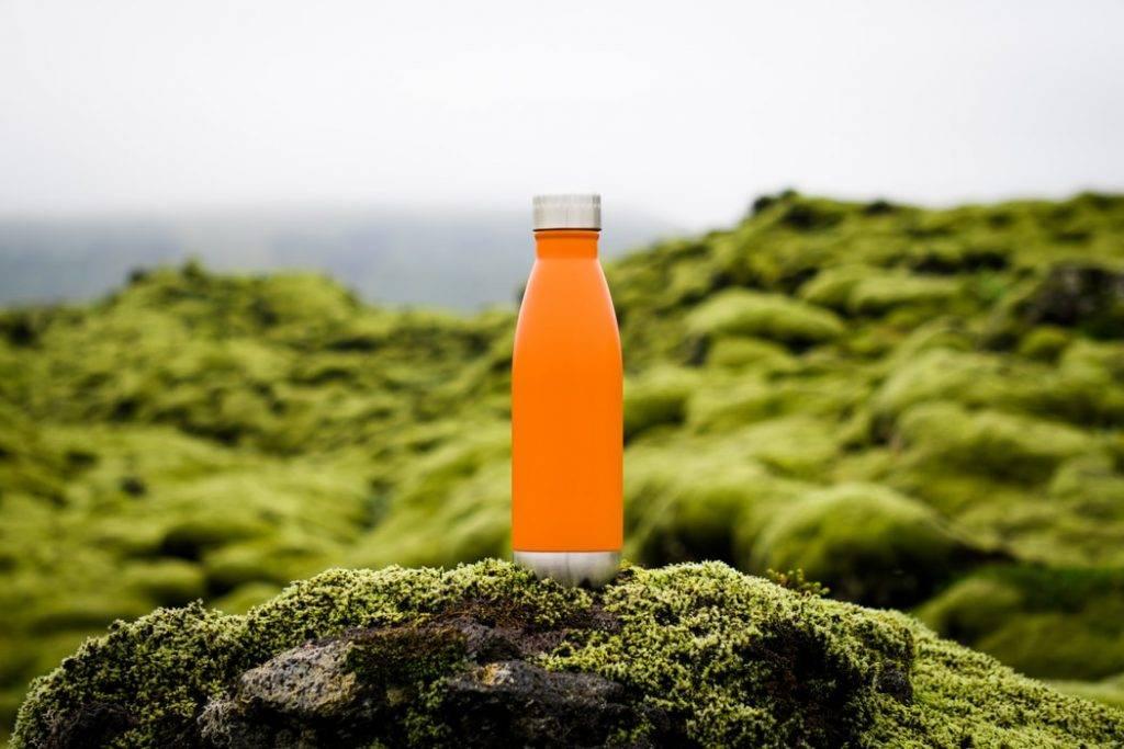 Orange vattenflaska på sten med mossa i naturen på klippiga berg av mossa