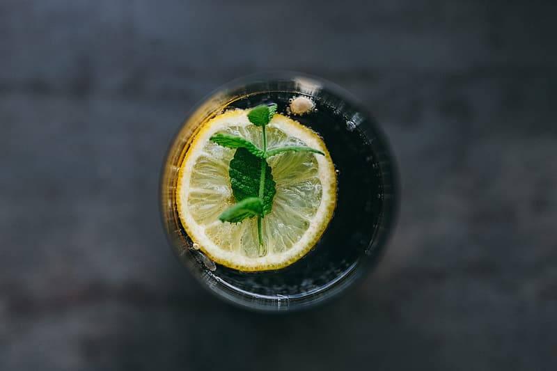 vattenglas med citronskiva och kvist med mynta fotat ovanfrån, drick lagom mycket vätska