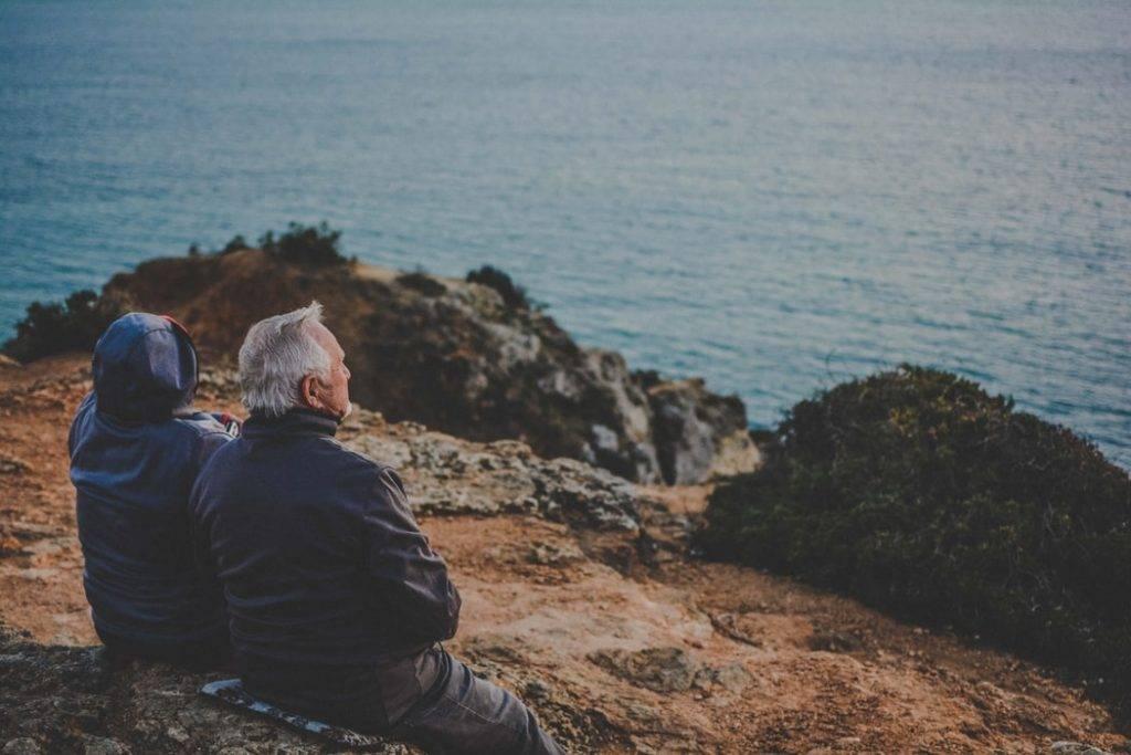 gammalt par sitter tillsammans på klippor framför havet och tittar ut, hälsosamma relationer