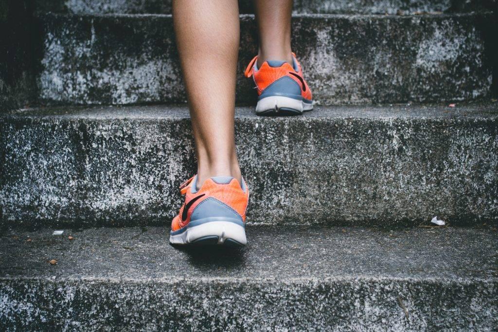 Kvinna promenerar uppför stentrappor med färgglada träningsskor, promenader för hälsan