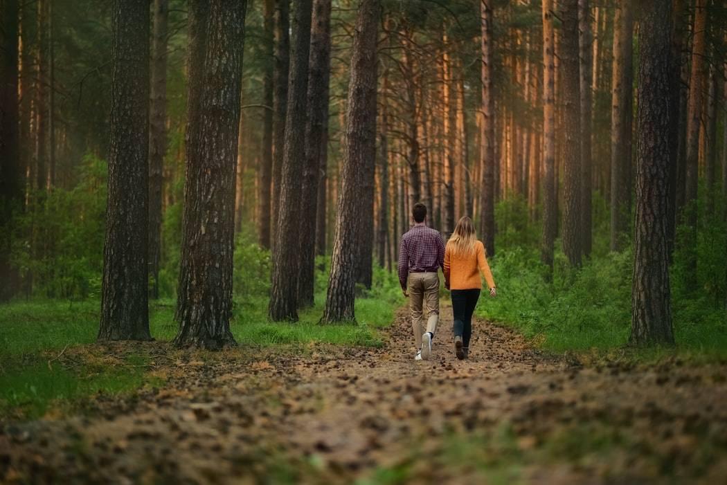 Kvinna och man promenerar i barrskog, Karolines way of life hälsoblogg