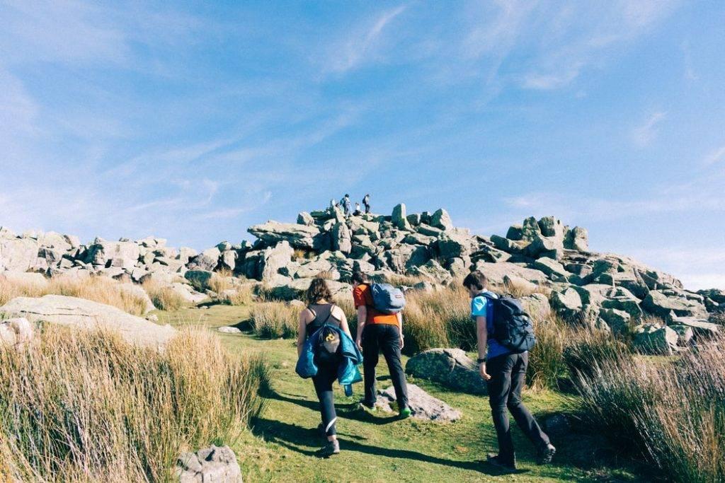 Killar och tjej går på vandring i bergen, hiking som är bra för hälsan