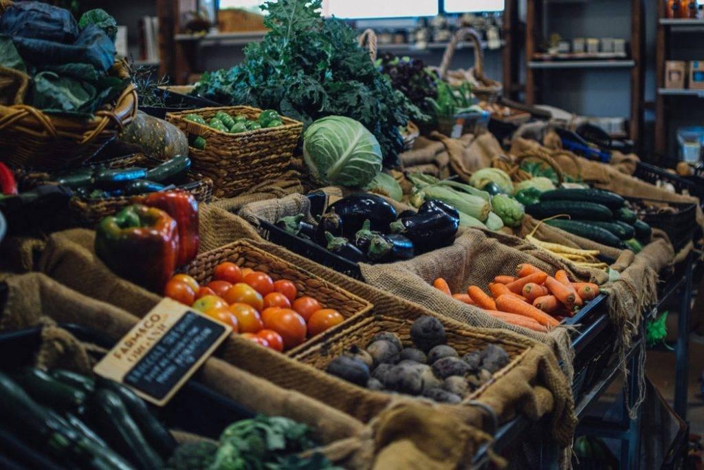 en liten grönsaksbutik har olika grönsaker i trälådor med grova säckar i lådorna där grönsakerna ligger. Bra för att stärka hälsa i ett hälsoorienterat samhälle.