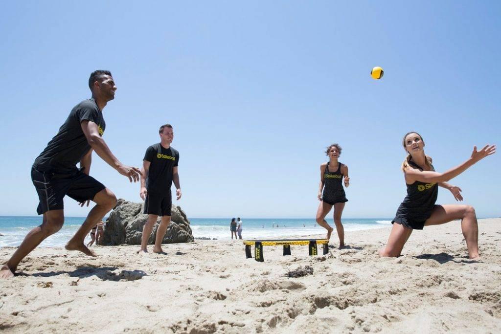 kvinnor och män spelar boll på strand i solen