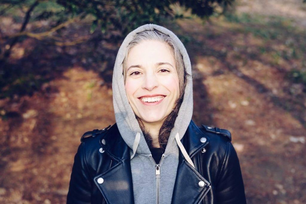 Kvinna i grå hoodie och svart läderjacka med luva över huvudet. Svart och grått hår och hon har ett stort leende på läpparna. Står i en skog eller naturen i höst eller vårsol.
