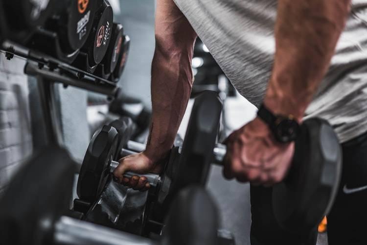 man lyfter hantlar dumbbells på gymmet som styrketräning