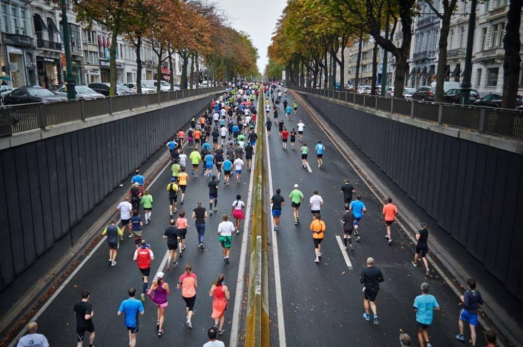 många människor i färgglada träningskläder springer gatulopp i stad på asfalt. Hälsopromotion i ett hälsoorienterat samhälle.