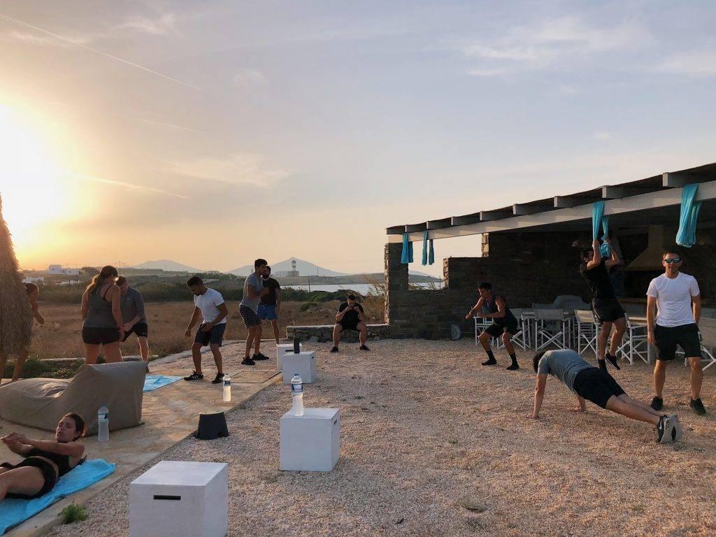 kvinnor och män tränar cirkelträning styrketräning utomhus på kvällen eller morgonen