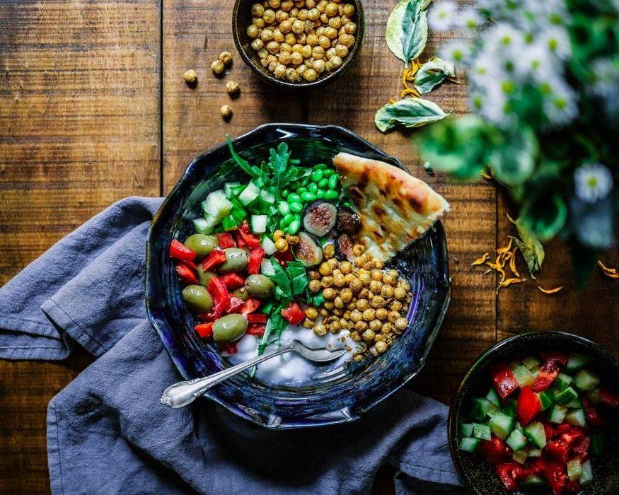 skål med grönsaker och bönor på träbord med blommor, hälsosam mat