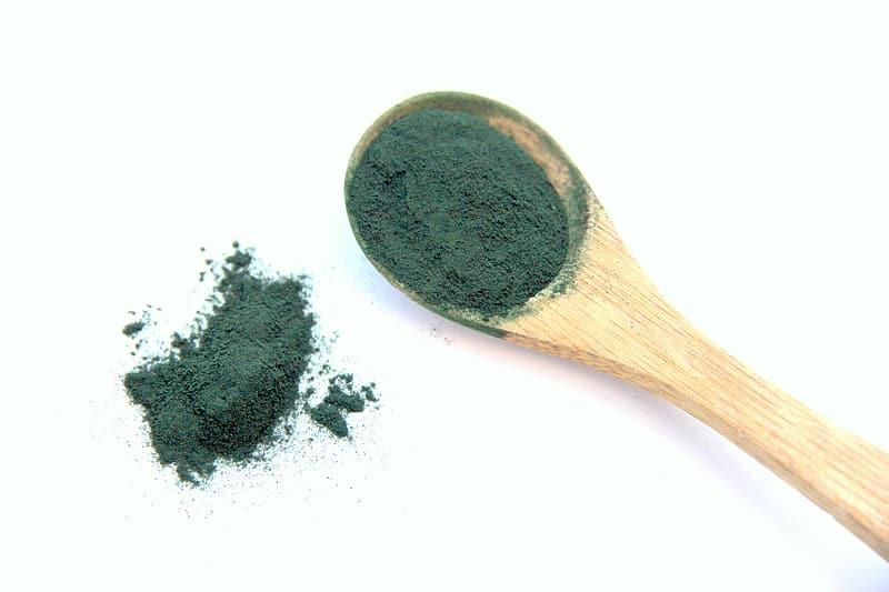spirulina pulver på träsked som kosttillskott