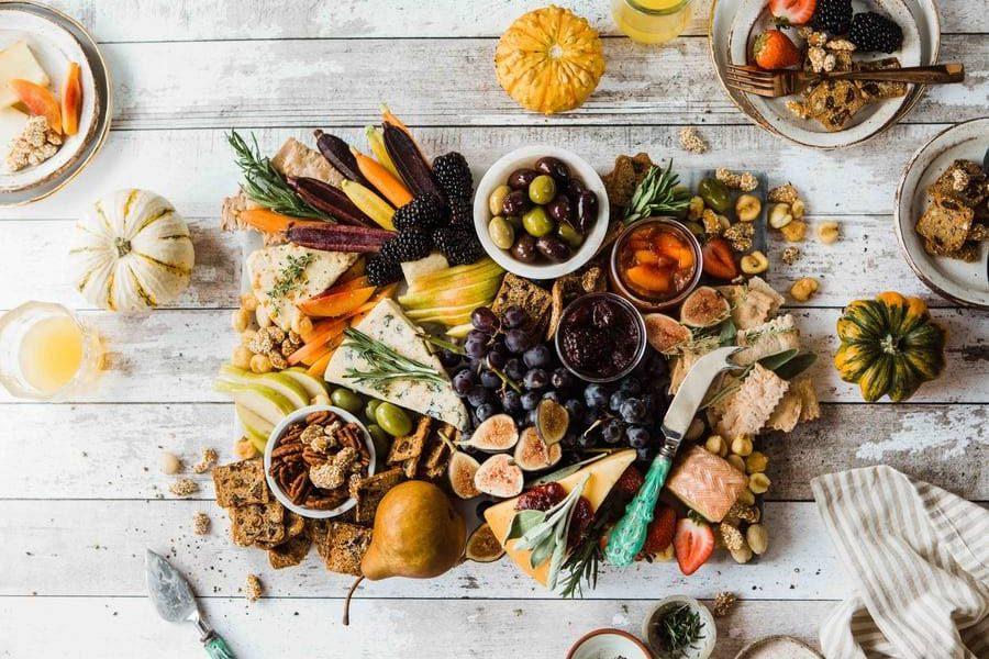 näringsrik mat, grönsaker, nötter, ostar och frukter på bräda på vitt bord med skålar av snacks, varierad näringsrik kost som positivt påverkar immunförsvaret