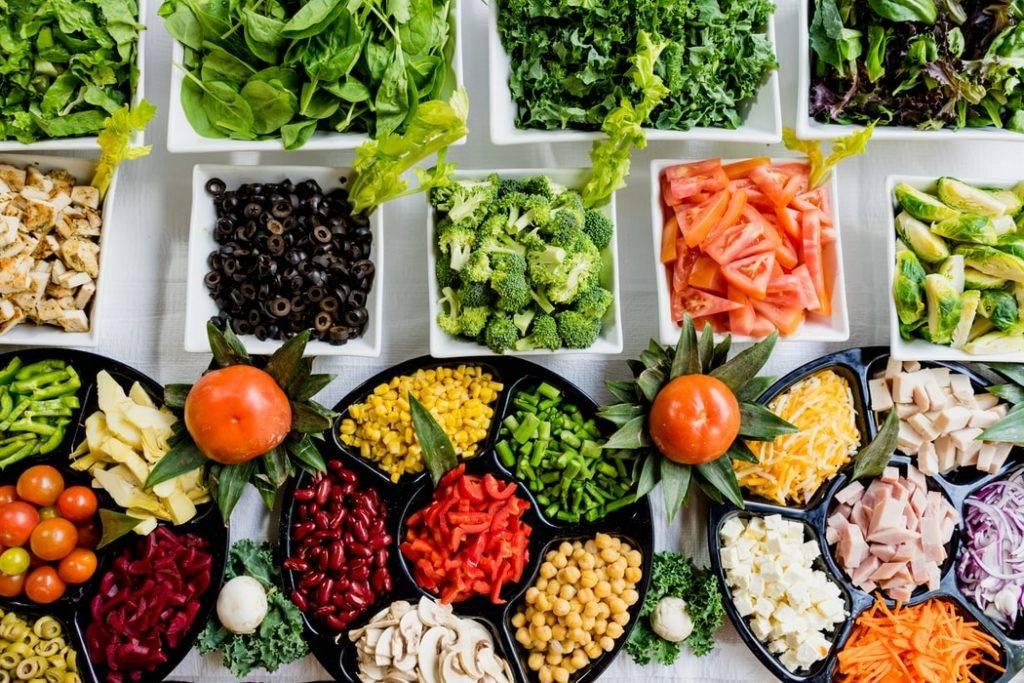 hälsosam mat, grönsaker, bönor, kött och ost upplagda i skålar på bord är kost som påverkar och stärker tarmfloran och immunförsvaret