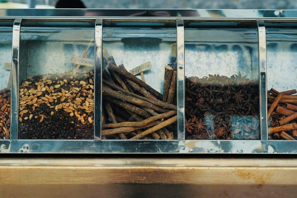 Lakritsrot, stjärnanis, kanelstänger och andra frön ligger i rad i sammanhängande glasburkar i butik. Lakrits är en adaptogen ört som motverkar stress och stärker hälsan
