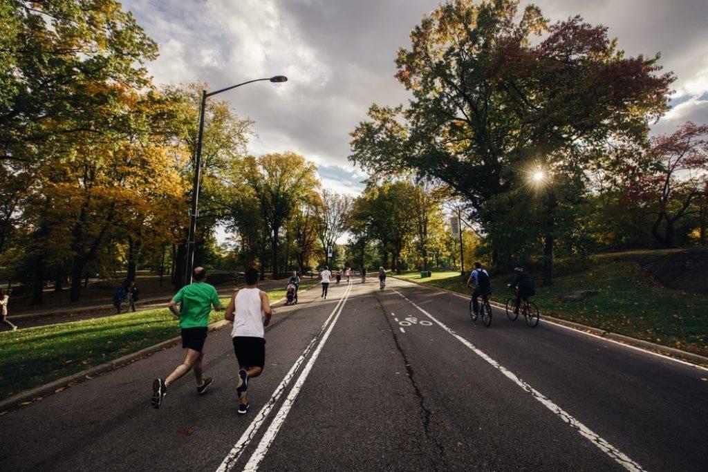 människor springer, cyklar och promenerar en varm solig dag utomhus på asfalterad gång och cykelväg med träd och buskar vid sidan. Fysisk aktivitet påverkar immunförsvaret positivt