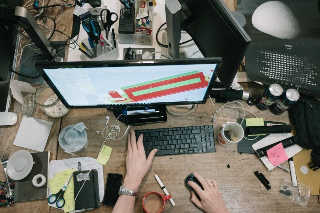 person sitter framför dator på ett stökigt skrivbord med saker överallt. Det står koppar med kaffe och ligger papper över hela bordet.