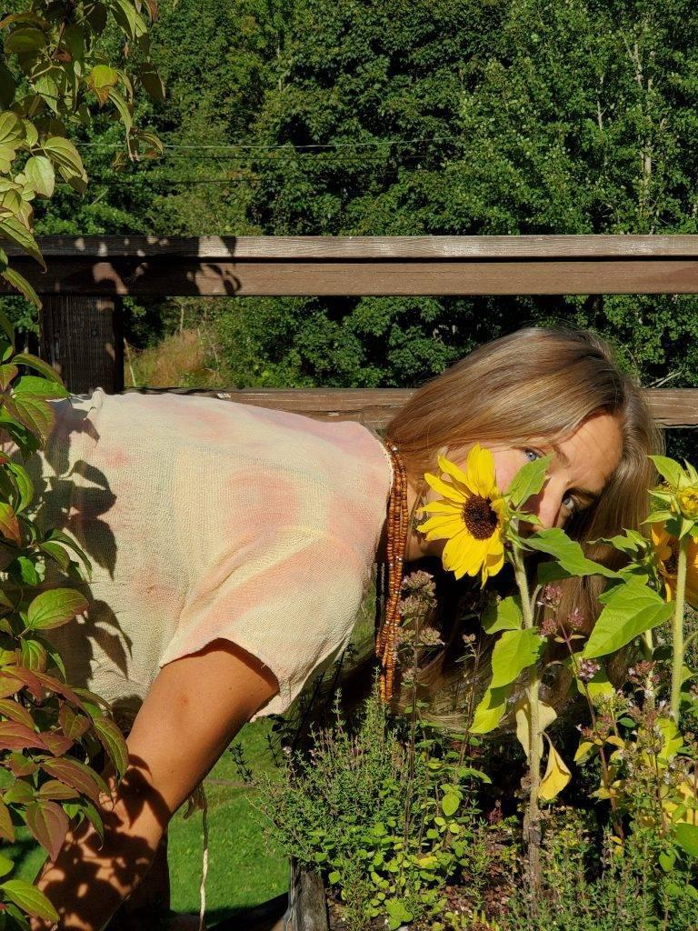 Karoline Karttunen böjer sig fram och tittar fram bakom en gul solros i upphöjd rabatt. Det är grön växtlighet runtomkring och skog bakom. Tröjan är batik med orange och gult. Det hänger ett trähalsband från halsen