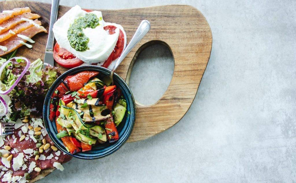 grönsaker, lax. nötkött och ost ligger på en skärbräda av trä, tillsammans med en mörkblå och svart liten skål samt kniv och gaffel. I skålen ligger rostad paprika och avokado med balsamico ringlat över. Det ligger mozarella med tomatskivor och persto ovanpå. laxen är skivad med sås ringlad ovanpå. På köttet ligger skivad parmesan och pinjenötter. Bredvid köttet ligger salladsblad med ringar av rödlök. Kostfibrer är födan till tarmbakterierna.