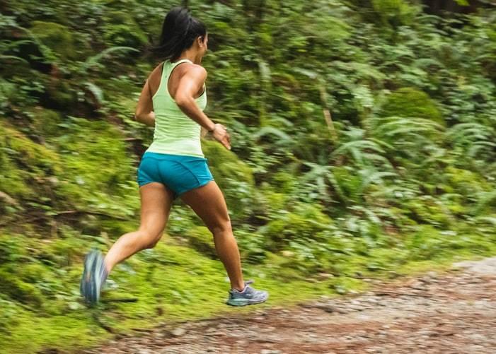 kvinna med svart hår uppsatt i hästsvans springer på stig i skogen. Hon har på sig ett par blåa korta shorts och ett tight ljusgrön sportlinne. Bilden är tagen när båda fötterna är i luften och armarna rör sig på sidan