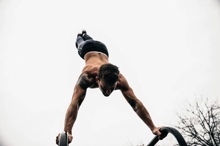 man gör handstand på två stänger. Håller stänger runt händerna och resten av kroppen är ovanför. Mannen har bar överkropp och tatuering på axeln, svarta tighta byxor. Gymnast