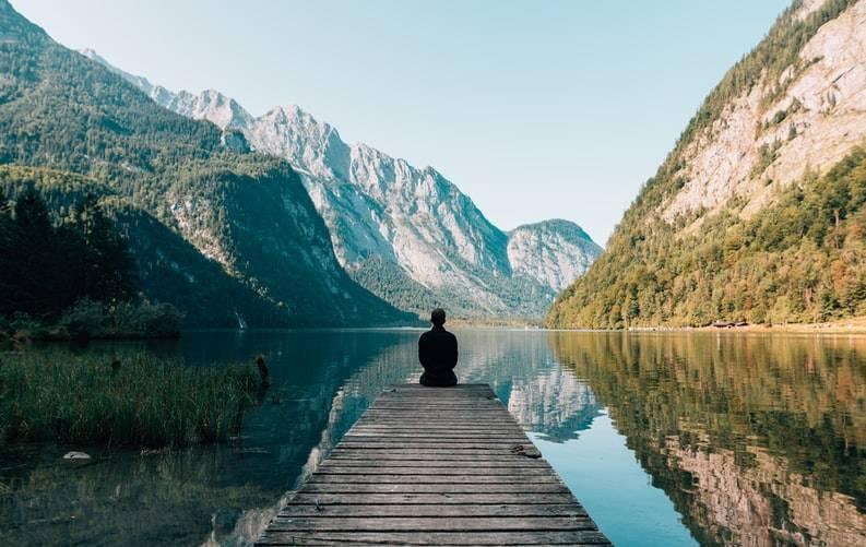 person sitter på en träbrygga och tittar ut över vatten, berg och dal. Bergen är klädda med skog och växtlighet. Vattnet ligger stilla och går mellan bergen och dalen. Varva ner vid överträning