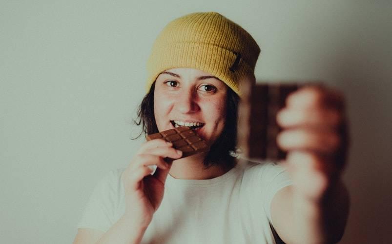 Tjej med brunt kort hår i page och gul mössa på huvudet håller choklad. En chokladkaka i ena handen som hon håller upp framför kameran. Den handen är ur fokus och suddig. Den andra handen håller en annan bit choklad som hon har i munnen, med ett leende och tittar in i kameran.