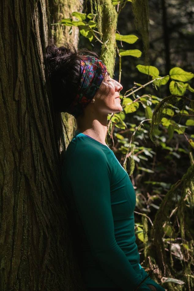 Kvinna i grön långärmad tröja och färgglatt hårband/pannband runt håret, som är uppsatt, står lutad mot ett träd i naturen i skogen. Hon blundar och tittar upp mot solen som lyser i hennes ansikte. Trädet är stort med en grov tjock stam och gröna blad på sina grenar.