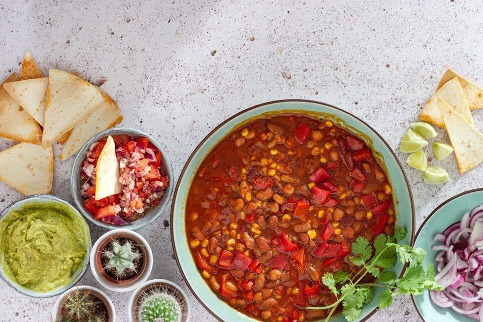 böngryta med kött och paprika ligger i en stor skål på ett vitspräckligt bord. Rundomkring står små skålar med olika grönsaker och tre små krukor med kaktusar. I en skål ligger gaucamole, en skål med skivad rödlök, en skål med tomatsallad och ett tortillaships. På bordet ligger det tortillachios och uppskuren lime. I grytan ligger några kvistar med koriander. Mer frukt och grönsaker i kosten