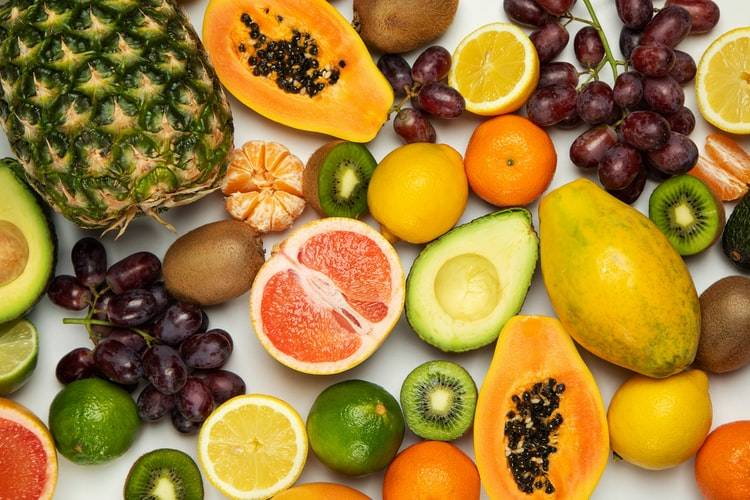 Frukter ligger på ett vitt bord. Vissa är hela och andra är delade i mitten. Apelsin, kiwi, vindruvor, blodapelsin, avokado, papaya, citron, clementin, ananas och lime. Mer frukt i kosten