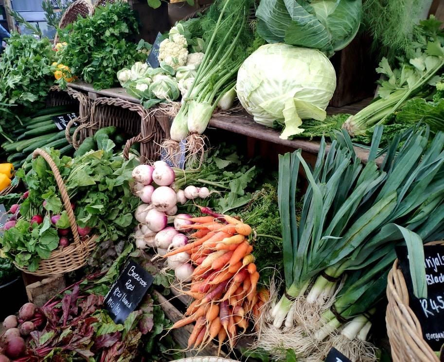 Grönsaker och rotfrukter på hyllor som består av trälådor och korgar. Uppställda framför varandra på marknad. Korgarna och hyllorna är fulla med färska grönsaker; rödbetor, rädisor, vitkål, morötter, purjolök, blomkål, celleri, persilja, bladgrönsaker, lök, paprika, gurka, salladsblad.