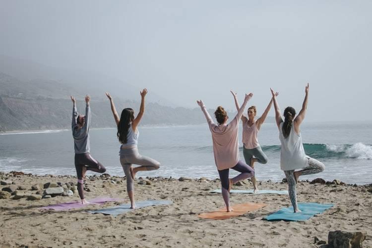 """grupp på 5 personer gör yoga på en strand. De står på varsin yogamatta i """"trädet"""" med ena benet i knävecket på det andra benet samt båda armarna rakt upp ovanför huvudet. Yogalärarens står vänd mot de deltagande. Hon står med ryggen mot vattnet och de andra står vända mot vattnet. Det är en liten våg vid strandkanten. Rolig träning"""