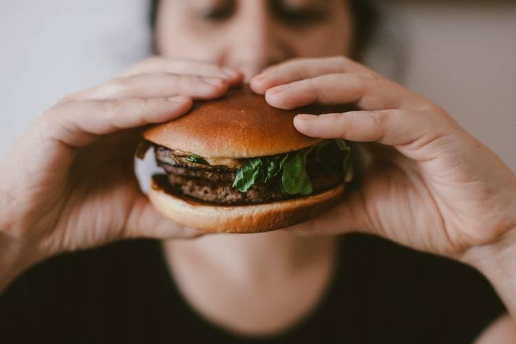Kvinna suddig i bakgrunden med händerna framför kameran. I händerna håller hon en hamburgare med vitt bröd, hamburgekött och sallad. Kvinnan tittar på hamburgaren och håller båda händerna runt den.