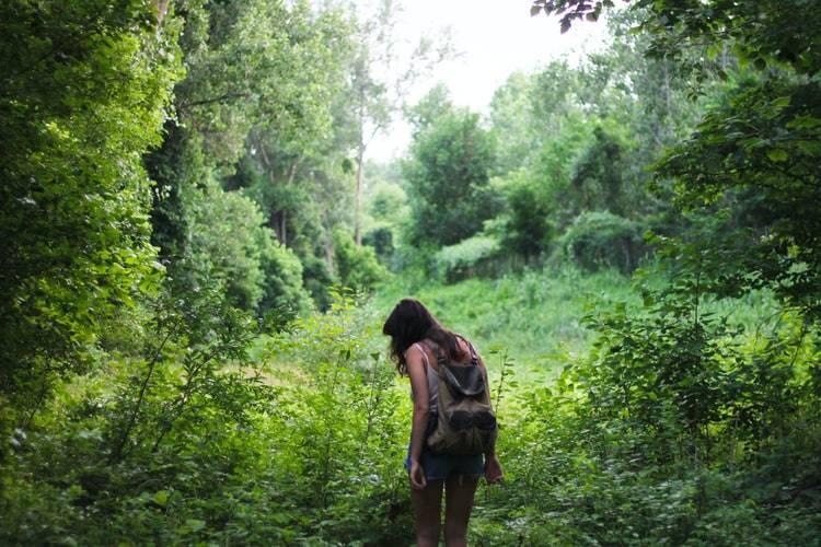 Kvinna med linne, tights och ryggsäck på ryggen går i grön lummig skog. Tjejen har brunt utslöppt hår och tittar snett nedåt. Runt henne är det grön lummig bladskog med bladträd, buskar och växtligheter. En fin sommardag