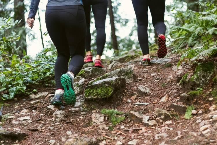 tre personer promenerar i skogen med träningskläder och träningsskor. De går på en upptrampad stig med många stenar. Det är gröna buskar och träd kring stigen.
