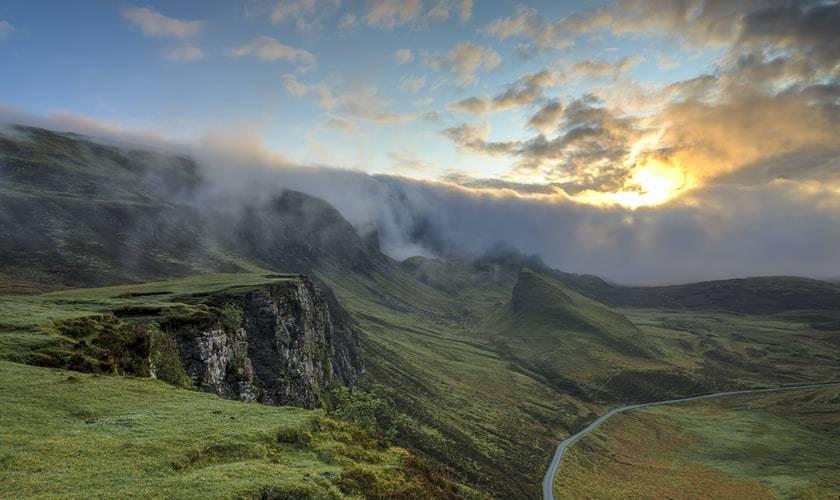 vy över grönaklädda berg med en fors som rinner längst med dalen. Det är gryning eller skymmning och solen syns precis vid toppen av berget. kring horisonten. Runt solen och toppen av bergskedjan slingrar sig vita moln.