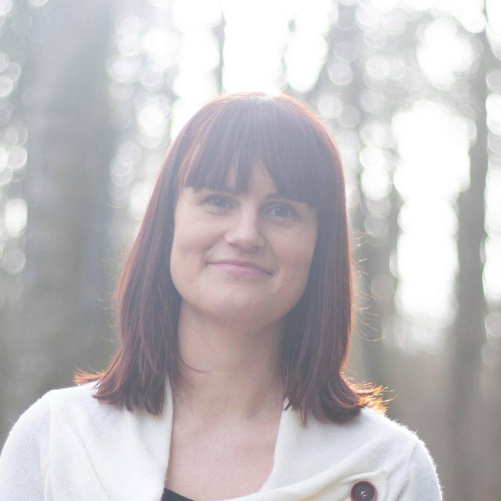 Annika Rosenqvist för SensiVeda Hälsoutveckling. Bilden är tagen framifrån på Annikas ansikte och en bit av överkroppen. Hon har på sig en vit kofta över en svart tröja och brunt hår till axlarna. Annika har lugg och leer utan att visa tänder medan hon tittar in i kameran. Bakom henne syns skog och träd.