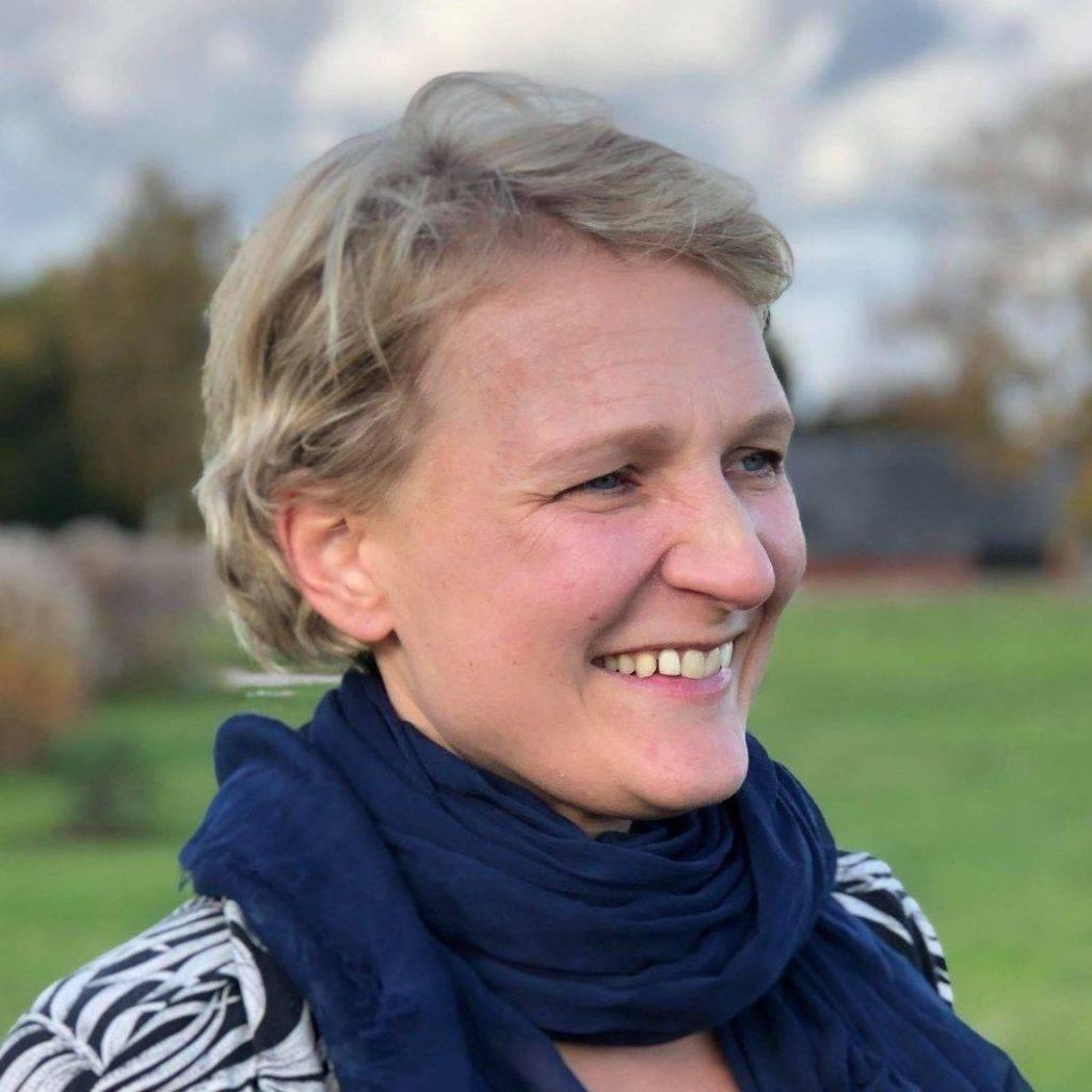 Ida Engström för Power of Senses. Bilden är tagen på hennes ansikte då hon tittar åt sidan. Ida har på sig en vit och svartrandig tröja och en mörkblå sjal runt halsen. Hon har kort blont hår och leer stort. I bakgrunden syns natur ur en suddig vinkel.